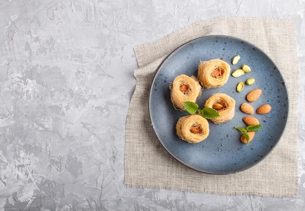 Kunafa, dolci arabi tradizionali nella vista superiore del piatto ceramico blu.