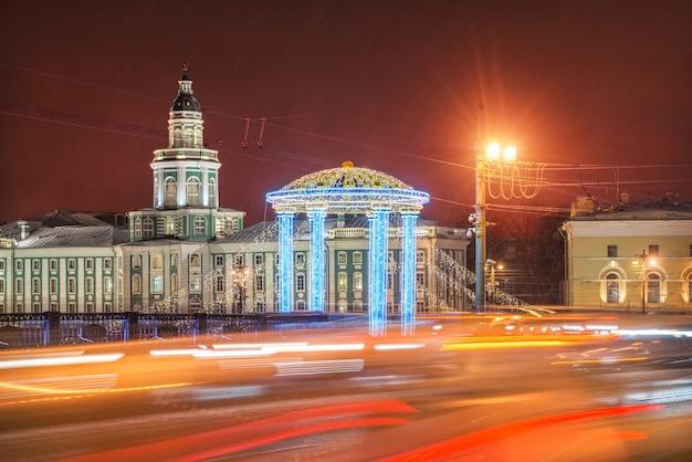 Kunstkamera e la decorazione di capodanno del ponte del palazzo a san pietroburgo alla luce delle luci notturne delle auto