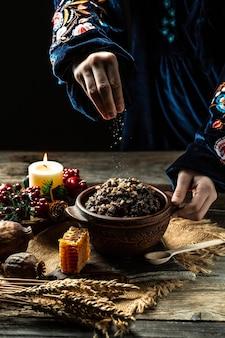 Kutya, candele e decorazioni natalizie su un tavolo di legno