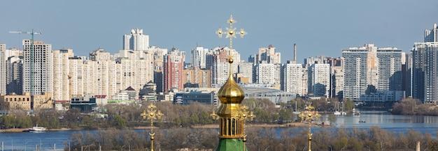Kiev, ucraina - 28 aprile 2021: monastero di vydubychi. cupole del monastero cristiano. vista della città di kiev dal giardino botanico. fiume dnieper e nuovi edifici della grande città