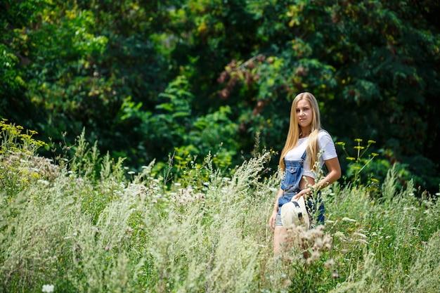 Kyiv, ucraina - agosto 2019 giovane bella ragazza in tuta di jeans e un cappello leggero che cammina nel parco