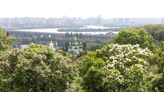 Kiev, ucraina - 10 maggio 2019: vista del monastero di vydubychi, del fiume dnipro e dei fiori lilla nel giardino botanico nazionale di hryshko a kiev.
