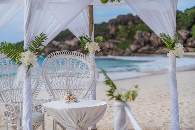 La digue, seychelles. cerimoniale di gazebo ad arco per matrimoni decorato con fiori bianchi su una spiaggia di sabbia tropicale di grand anse. famose pietre di granito.