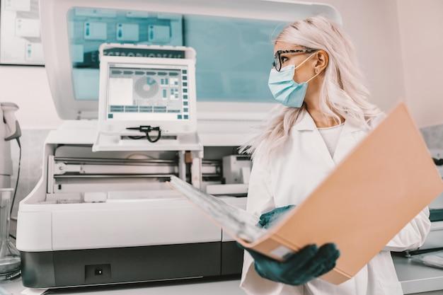 Assistente di laboratorio che esamina la cartella con i documenti. concetto di focolaio del virus corona.