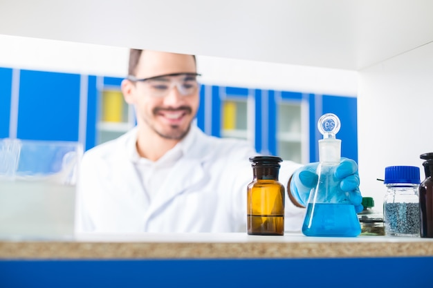 Laboratorio all'interno. messa a fuoco selettiva della mano maschile prendendo bicchieri da laboratorio con liquidi versati e in piedi sulla superficie