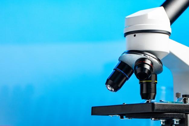 Fine del microscopio del laboratorio in su contro priorità bassa blu