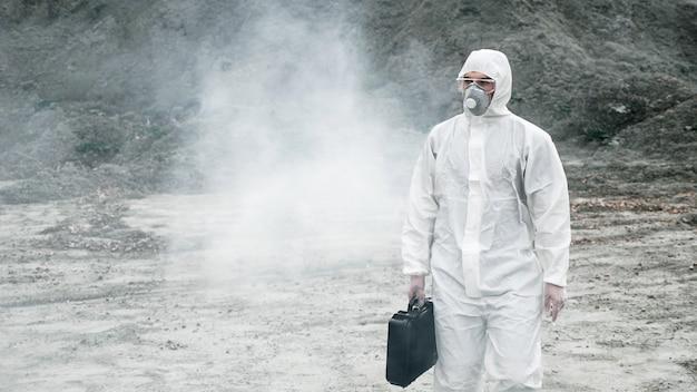 Tecnico di laboratorio in maschera e tuta di protezione chimica, cammina su un terreno asciutto con una cassetta degli attrezzi attraverso il fumo tossico.