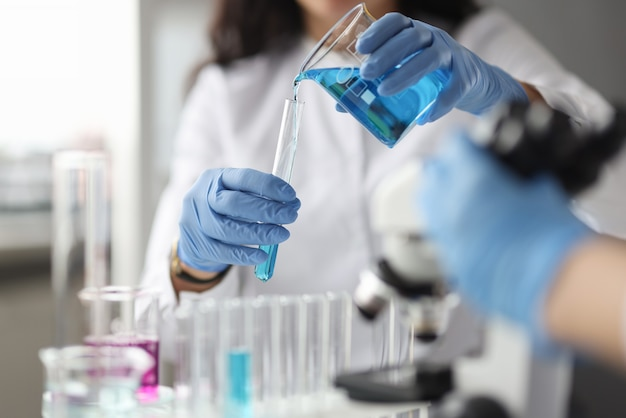 Il tecnico di laboratorio con i guanti versa il prodotto chimico nella provetta. ricerca scientifica in chimica