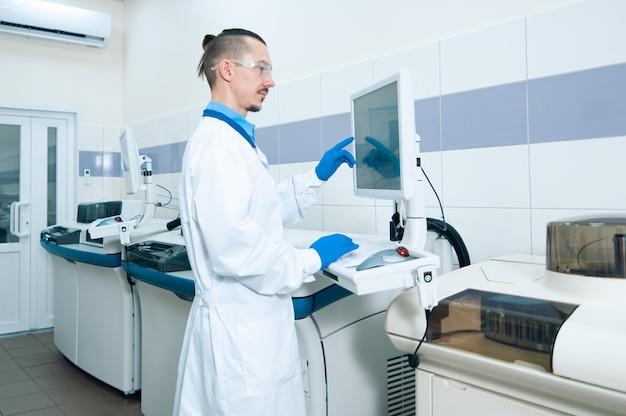 Assistente di laboratorio in guanti di gomma che lavora con un moderno analizzatore di immunochimica. concetto di ricerca di laboratorio medico, chimico o scientifico e innovazione in laboratorio.