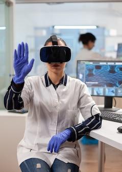 Medico di laboratorio che sperimenta la realtà virtuale usando gli occhiali vr