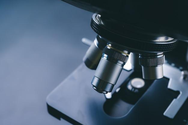 Microscopio ottico di apparecchiature di laboratorio, primo piano del microscopio scientifico con lente in metallo, analisi dei dati in laboratorio