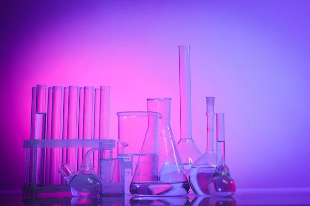 Vetro da laboratorio per chimica o medicina per la ricerca. natura morta nei toni del rosa, viola e blu