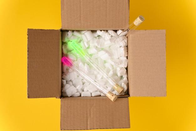 Palloni di vetro da laboratorio pieni di liquido luminoso in una scatola di consegna