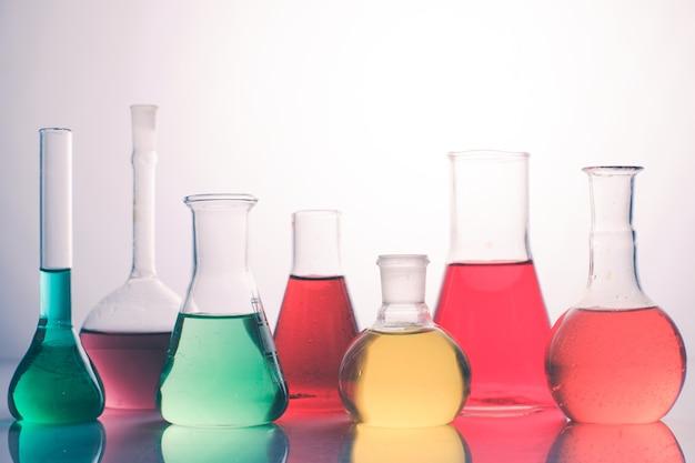 Vetro da laboratorio con liquidi color arcobaleno, natura morta chimica