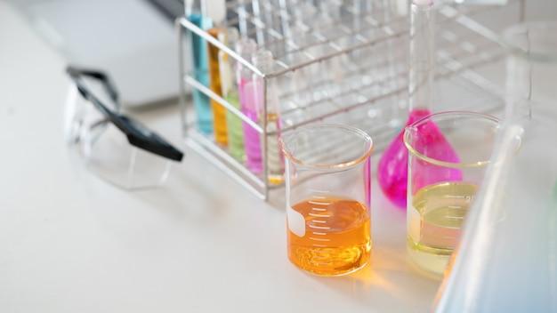 Vetreria di laboratorio contenente liquidi colorati e occhiali di sicurezza.