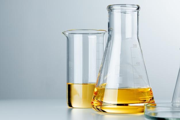 Vetreria per laboratorio con liquido oleoso giallo su fondo grigio