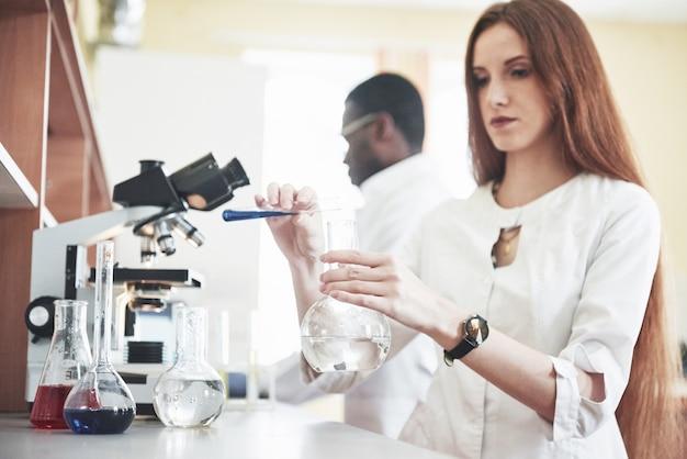I laboratori di laboratorio conducono esperimenti in un laboratorio chimico in fiasche trasparenti. formule di output.