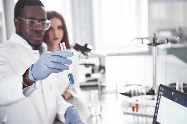I laboratori di laboratorio conducono esperimenti in un laboratorio chimico in boccette trasparenti. formule di output