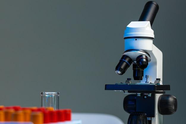 Il microscopio da laboratorio con le provette variopinte si chiude su