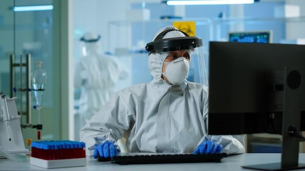 Assistente tecnico di laboratorio in tuta dpi che analizza il campione di sangue nella digitazione in provetta al pc. medico che lavora con vari batteri, tessuti, ricerca farmaceutica per antibiotici contro covid19.