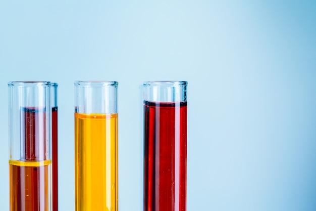 Provette di laboratorio con liquidi rossi e gialli su sfondo azzurro