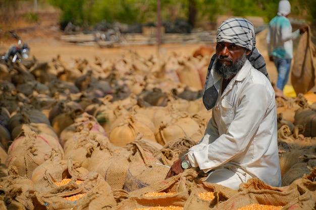 Braccianti che confezionano sacchi di iuta di mais