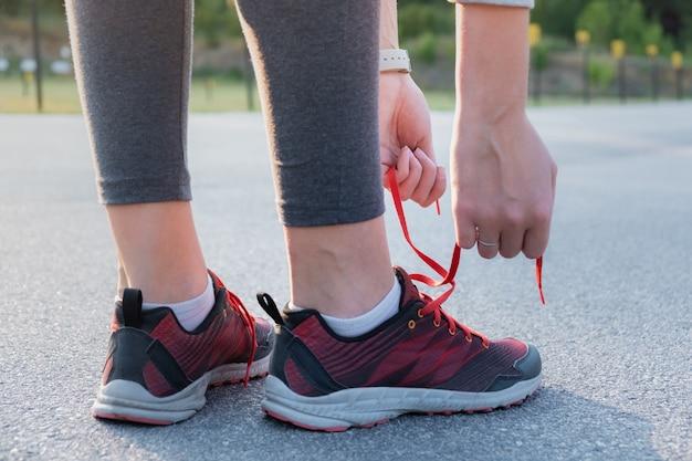 Allacciare le scarpe da corsa. primo piano delle mani della donna che allacciano le scarpe da ginnastica all'aperto in un parco