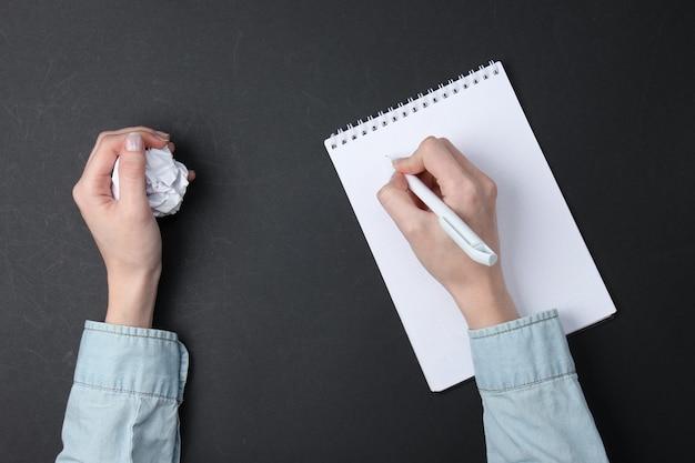 Mancanza di idee. le mani femminili scrivono in un taccuino e tengono una palla di carta spiegazzata su un nero.
