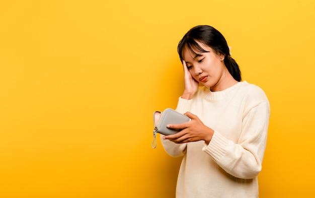 Mancanza di soldi problemi finanziari povera e povera donna asiatica che porta borsa vuota, problemi senza soldi in debito, spese, isolate su sfondo giallo.