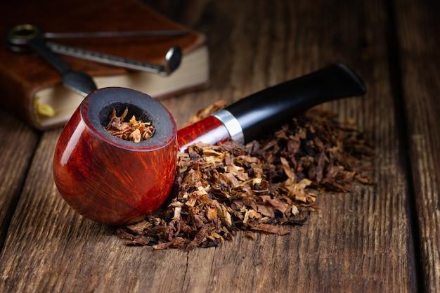 Pipa da fumo laccata e mucchio di tabacco sul tavolo in legno d'epoca. copia spazio.