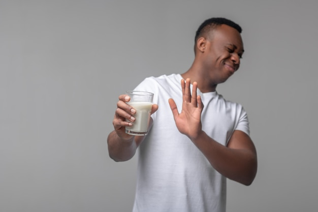 Intolleranza al lattosio. giovane adulto uomo nero con una smorfia che rifiuta un bicchiere di latte gesticolando mentre si trovava in studio