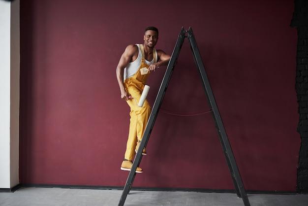 Sulla scala. il giovane operaio afroamericano in uniforme gialla ha qualche lavoro