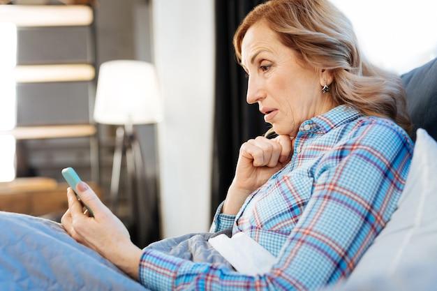 La signora è contenta. trasmettendo una bella donna adulta che riposa a letto la mattina e osservando le notizie sul dispositivo elettronico