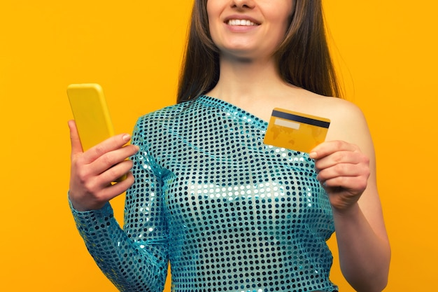 Signora che acquista online con carta di credito e smart phone su sfondo giallo