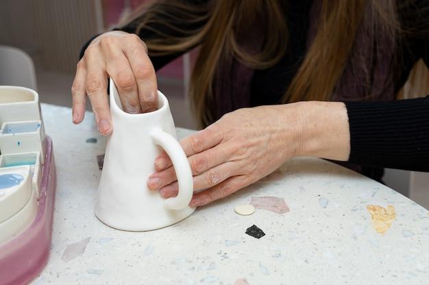 La signora pulisce la brocca bianca con carta vetrata prima di applicare il motivo alla brocca di latte di argilla in officina