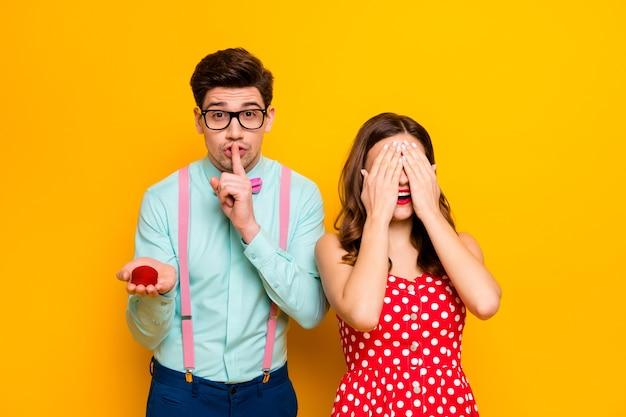 La signora chiude gli occhi il fidanzato le labbra delle dita tengono la scatola dell'anello della proposta a sorpresa