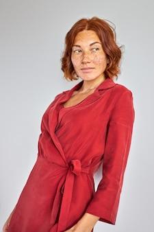 Signora in abito in posa vicino al muro in studio, donna rossa caucasica si è appoggiata al muro e distoglie lo sguardo