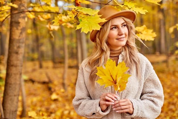 Lady godere di essere nella foresta d'autunno, la natura. bella donna bionda caucasica in cappello