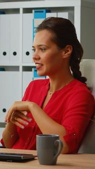 Signora che spiega le regole durante il webinar seduto davanti al computer dipendente che lavora con il team di lavoro in remoto discutendo di chat con conferenza online virtuale, riunione, utilizzo della tecnologia internet