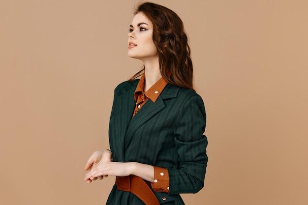 Signora in abiti di moda e sfondo beige acconciatura copia spazio