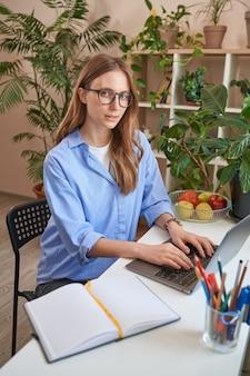 Signora con gli occhiali che usa il laptop mentre studia