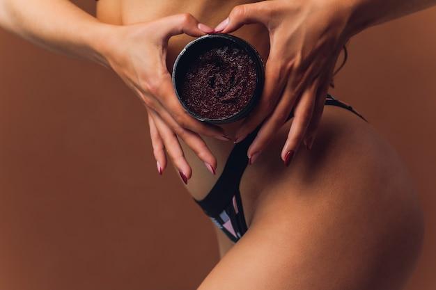 Signora mano sulla gamba spalmando crema mostrando un buon risultato in reggiseno rosa pallido isolato.