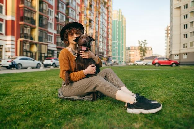 Signora in cappello che si distende sull'erba e sullo sfondo della città con il cucciolo in braccio