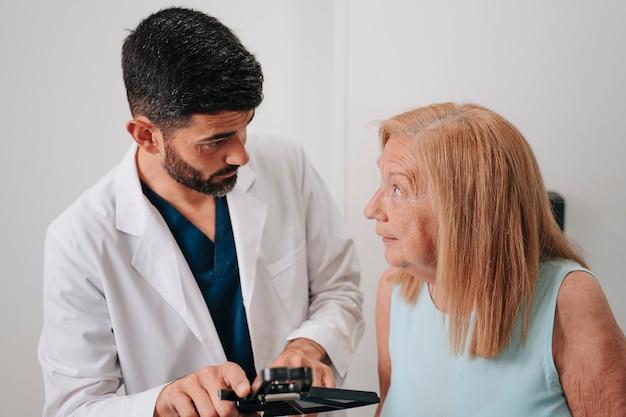 Signora sui 70 anni con l'aria sorpresa a un metro di pelle il grasso sul suo braccio accanto al suo nutrizionista