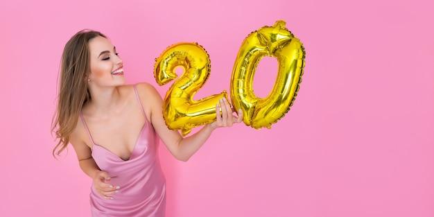 La signora tiene in mano palloncini di alluminio sotto forma di numeri con sconti del venti percento sulle vendite e cashback