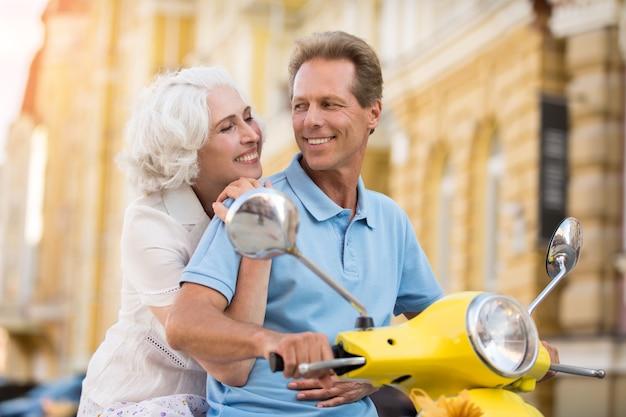 La signora abbraccia l'uomo sullo scooter.