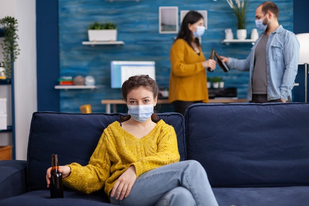 Signora che guarda la telecamera mentre trascorre del tempo con gli amici in soggiorno mantenendo le distanze sociali indossando una maschera facciale per prevenire la diffusione del coronavirus. durante l'epidemia globale tenendo la bottiglia di birra.