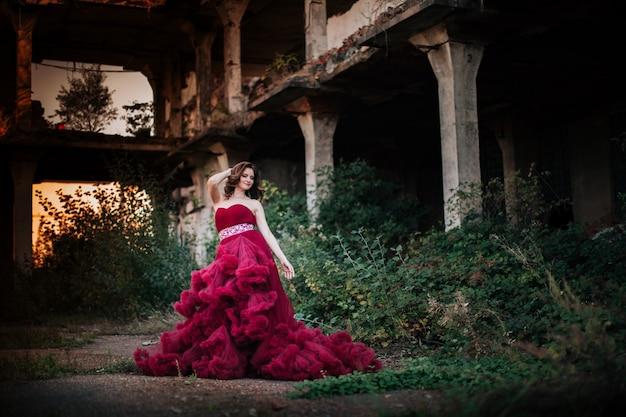 Signora in un vestito rosa lungo lussureggiante di lusso all'aperto. donna in abito rosso nuvoloso - simbolo di bellezza e rinnovamento della società