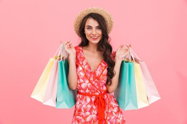 Signora che posa i sacchetti della spesa isolati della tenuta della parete.