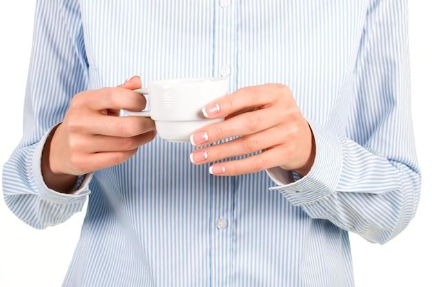 La mano della signora con la tazza da tè. l'impiegato femminile tiene la tazza di tè. buon umore in una tazza. stai calmo e bevi del the.
